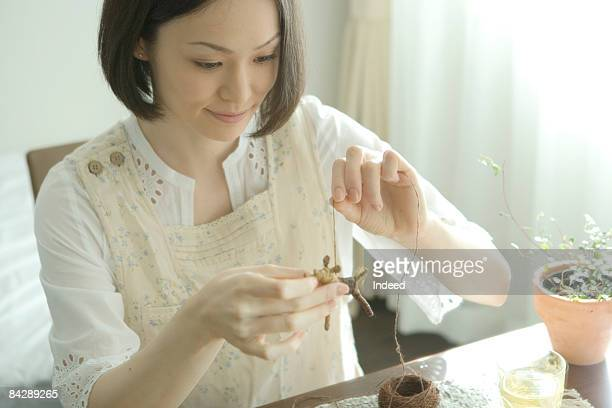 Japanese woman creating doll by string
