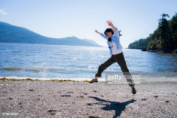 japanese woman doing cartwheel on beach - cartwheel stock pictures, royalty-free photos & images