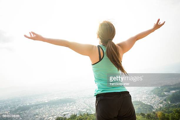 japanese woman doing yoga outdoors with arm raised