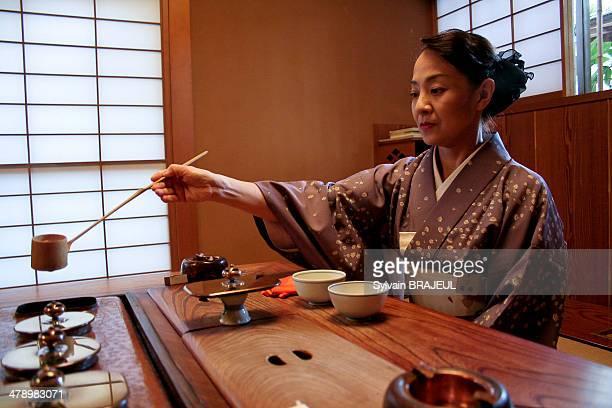 Japanese woman dressed in a kimono during a japanese traditional tea ceremony inside a Ryokan Kanazawa Honshu Japan