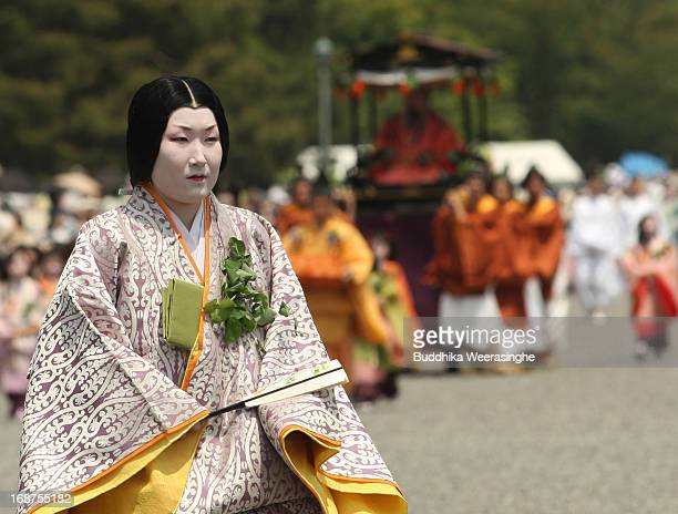 Japanese woman dressed in traditional costume walks in the procession of the Aoi Festival at the Imperial Palace on May 15 2013 in Kyoto Japan Aoi...