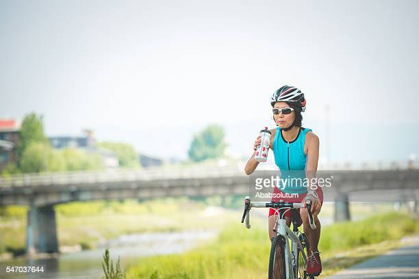 Japanese Woman Drinking Water while Riding Bike, Kamo River, Kyoto