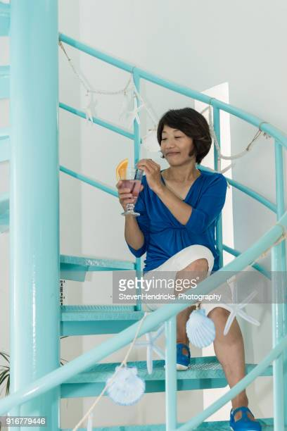 A Japanese woman drinks from a drink with a slice of orange in a cafe on a spiral staircase amongst sea shells draping from railing
