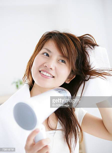Japanese woman drying her hair with hair dryer