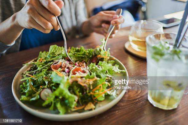 japanese woman eating a vegan lunch at a vegan cafe - 女性 ストックフォトと画像
