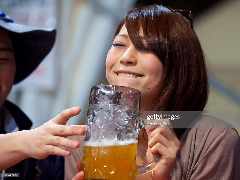 Japanese woman enjoying beer at Oktoberfest party.