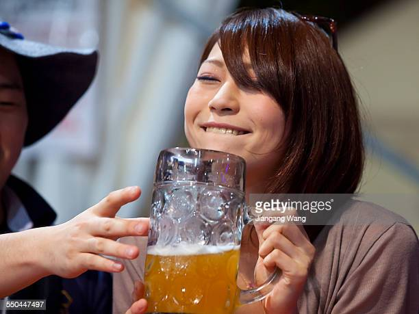 Japanese woman enjoying beer at Oktoberfest party