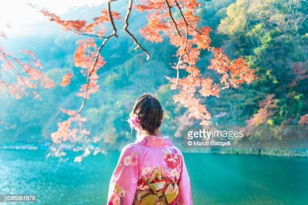 japanese woman enjoying koyo (autumn) season, arashiyama, kyoto, japan - quimono fotografías e imágenes de stock