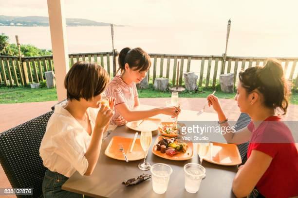 グアムのリゾート ホテルで友達と食事を楽しむ日本人女性