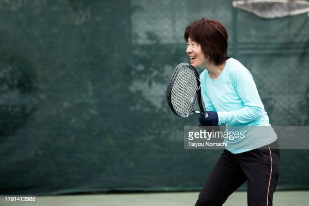 japanese woman enjoying tennis - racquet stock pictures, royalty-free photos & images