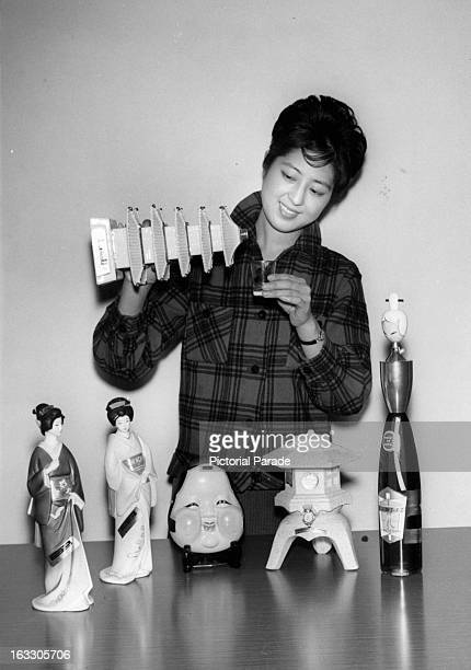 A Japanese woman features her novelty bottles representing pagodas geisha girls Noh masks and lanterns in Japan 1962