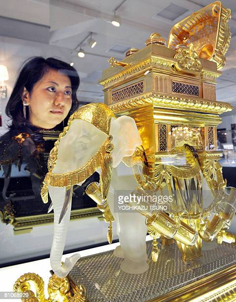 A Japanese woman gazes at an elephant shaped liqueur tantalus 66cm tall and weighing 57kg made by French luxury crystal maker Baccarat priced 63...