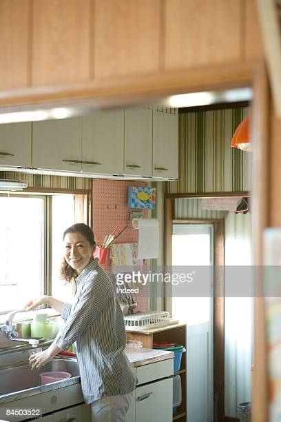 Japanese woman getting grass of water in kitchen