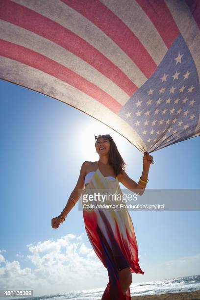 japanese woman holding american flag on beach - hawaii flag stock pictures, royalty-free photos & images
