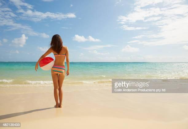 Japanese woman holding ball on beach