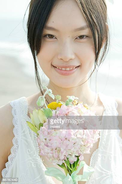 Japanese woman holding bunch of flowers, portrait