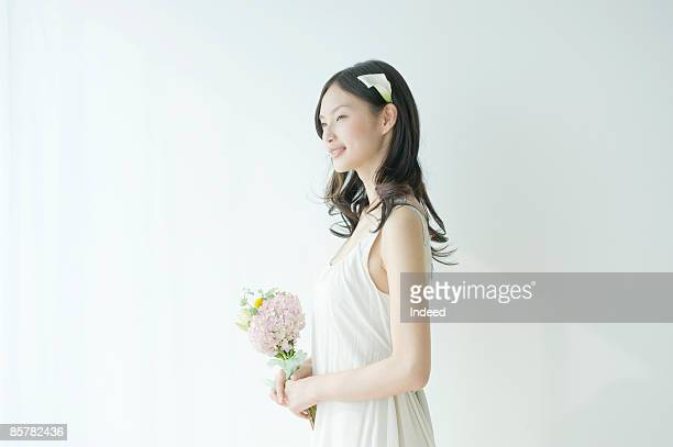 Japanese woman holding bunch of flowers, side view