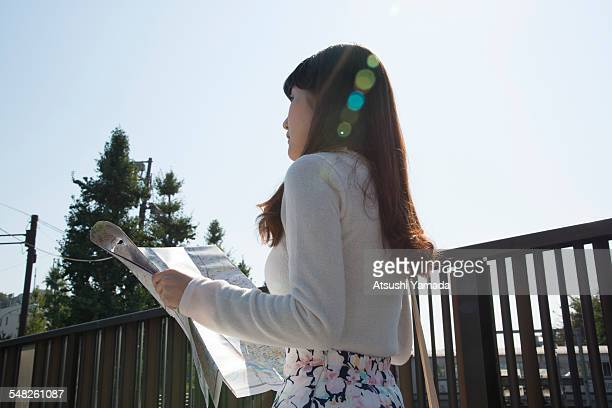Japanese woman holding map on street
