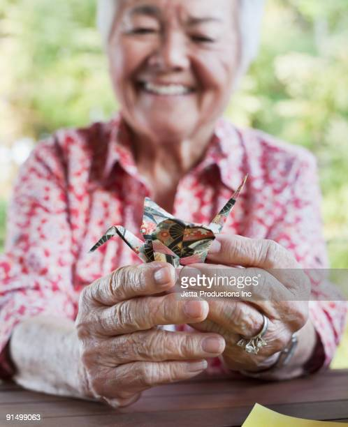 Japanese woman holding origami bird