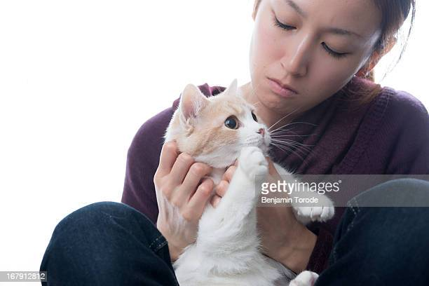 Japanese woman holding white and beige cat