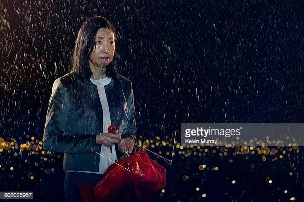 Japanese woman holds broken umbrella in rain