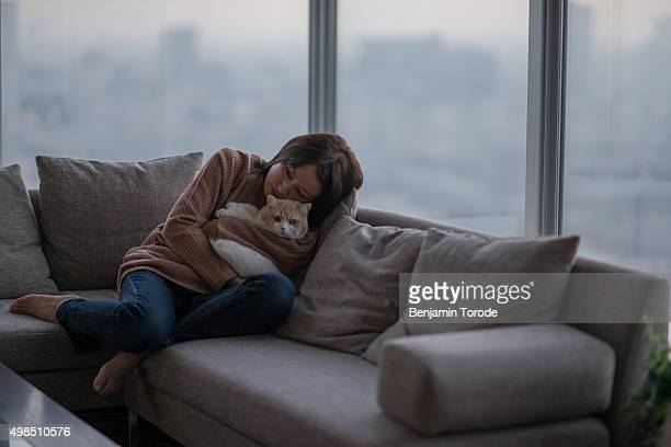 Japanese woman hugging cat on sofa in high-rise apartment