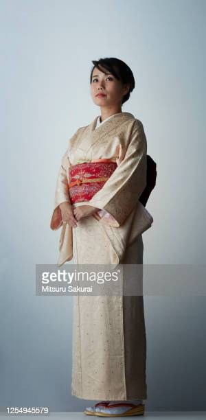 a japanese woman in a cool kimono against gray background - 女性 ストックフォトと画像