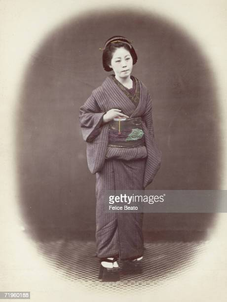 A Japanese woman in a padded winter kimono and embroidered obi or sash circa 1865