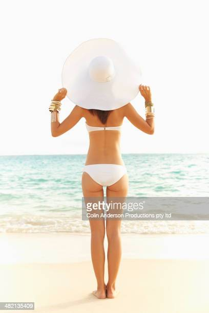 Japanese woman in bikini and sun hat on beach