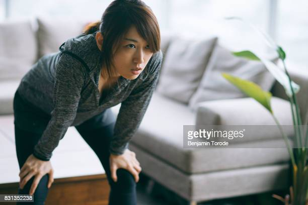 japanese woman in fitness attire bending over before starting exercise - bending over stock pictures, royalty-free photos & images