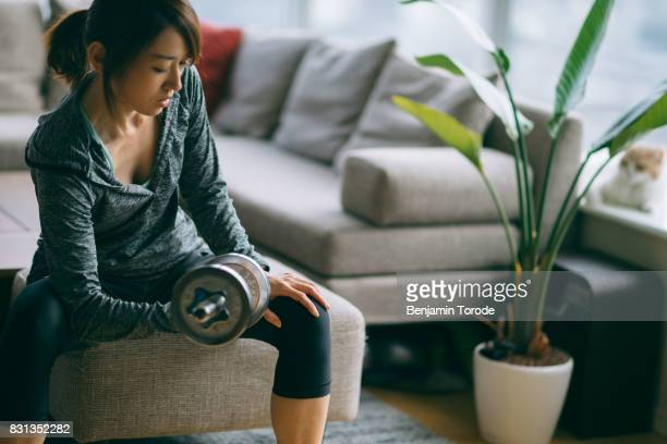 Japanese woman in fitness attire performing arm curls with dumbbell