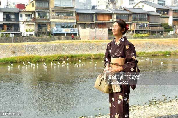 japanese woman in kimono walking along kamo river, kyoto - obi sash stock pictures, royalty-free photos & images