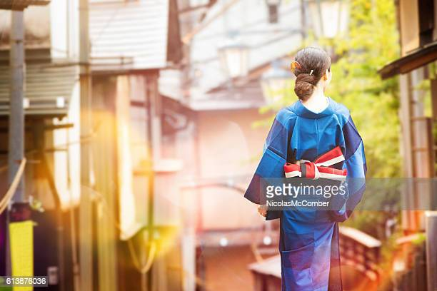 Japanese woman in kimono walking in village at sunset