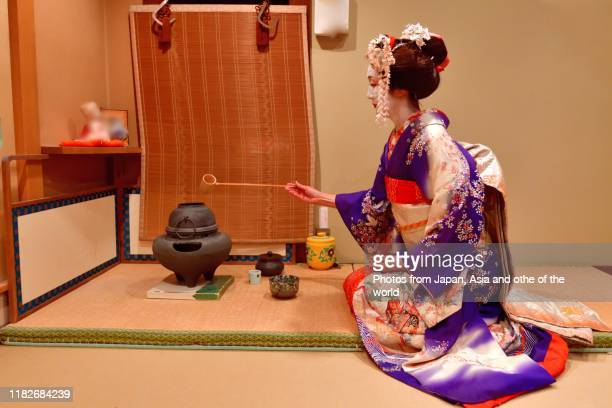 japanese woman in maiko's costume practicing tea ceremony at tea house, kyoto - ceremony stock pictures, royalty-free photos & images