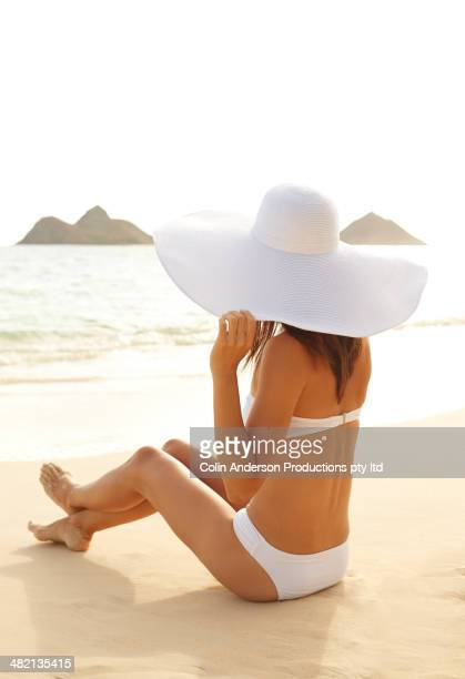 Japanese woman in sun hat and sitting on beach