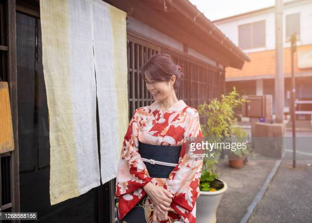 伝統的な日本料理店に入る浴衣の日本人女性 - のれん ストックフォトと画像