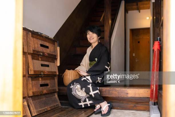 日本の伝統的な「旅館」ホテルの入り口に座る浴衣の日本人女性 - 宿屋 ストックフォトと画像