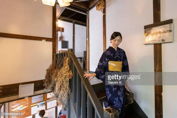 浴衣の日本人女性が日本の「旅館」ホテルで階段を下りる - 帯 ストックフォトと画像