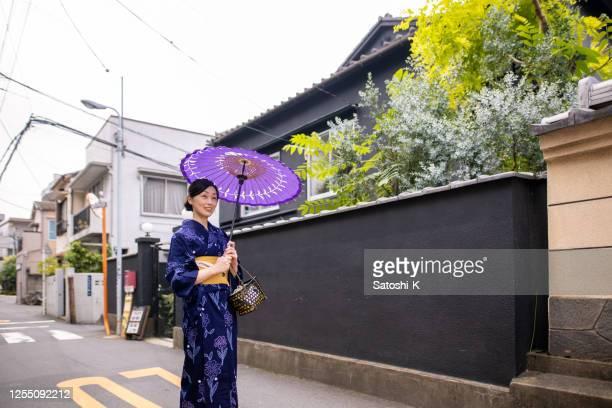 古い日本の町を歩く浴衣の日本人女性 - 帯 ストックフォトと画像