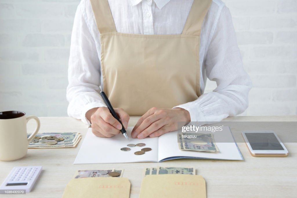 Japanese woman keeping household accounts with smart phone : Stock Photo