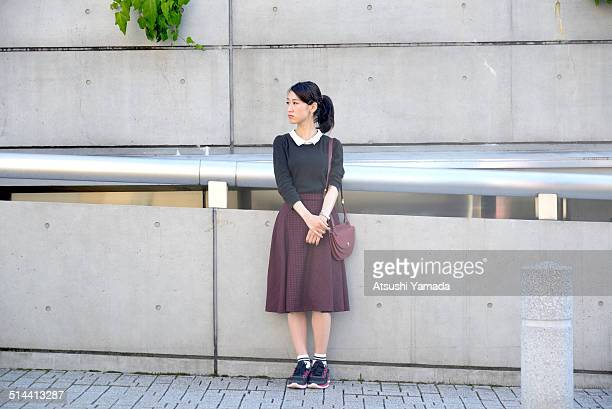 Japanese woman leaning against wall