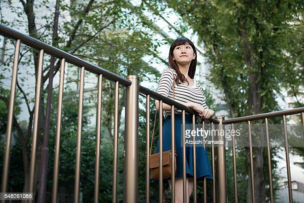 Japanese woman leaning on handrail