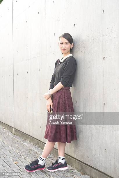 Japanese woman leaning on wall,holding cell phone