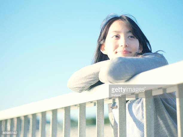 Japanese woman looking at view from bridge