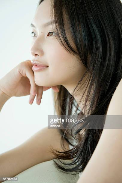 Japanese woman looking away, hand on chin
