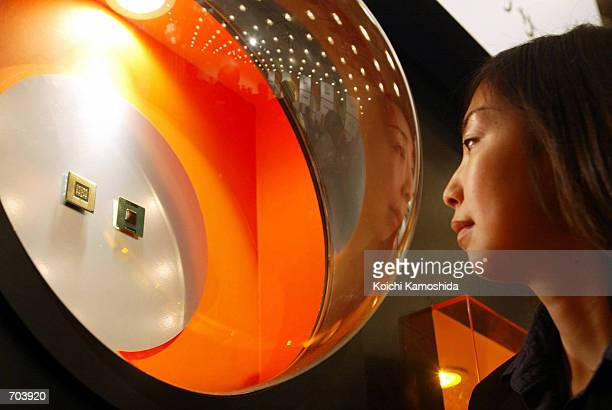 Japanese woman looks at The IntelR PentiumR 4 processor during a press conference March 1 2002 in Tokyo Japan The worlds top computer chip maker said...