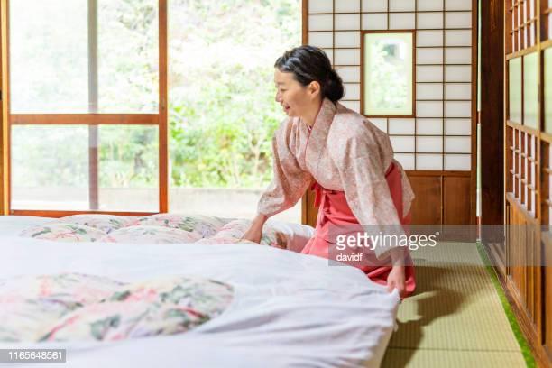 伝統的な布団を作る日本人女性 - 旅館 ストックフォトと画像