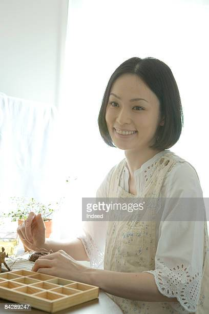 Japanese woman making doll, smiling