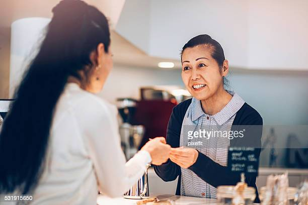 Japanese woman making payment with credit card in cafe