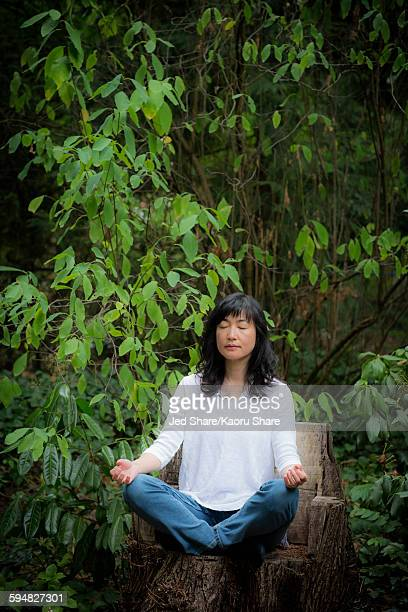 Japanese woman meditating in garden